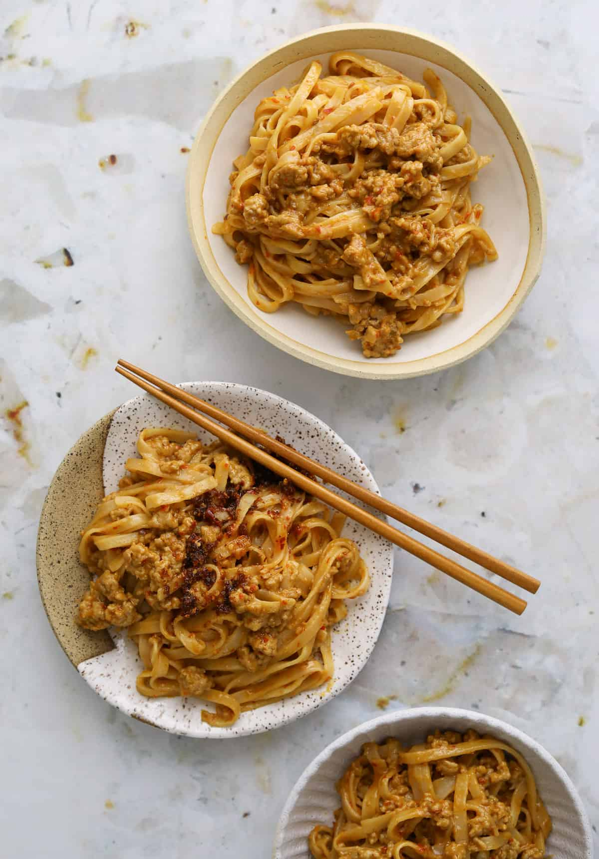 two bowls of spicy pork and peanut noodles in speckled ceramic bowls with wooden chopsticks on a stone marble background