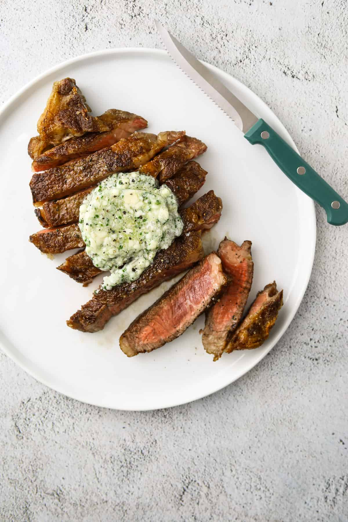 a white plate with sliced steak with a disk of melting compound butter and a blue steak knife on the side