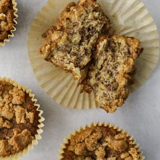 four almond flour banana muffins, one cut in half revealing a moist and fluffy center.