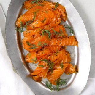 a silver plate of thinly sliced citrus cured salmon topped with fresh dil
