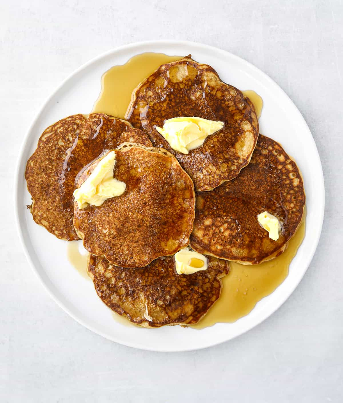 five oat flour pancakes on a white plate topped with butter and maple syrup