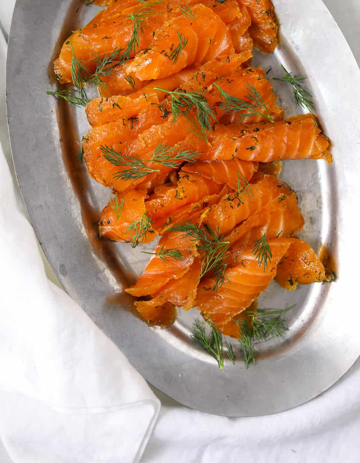 citrus cured salmon on a silver platter topped with fresh dill
