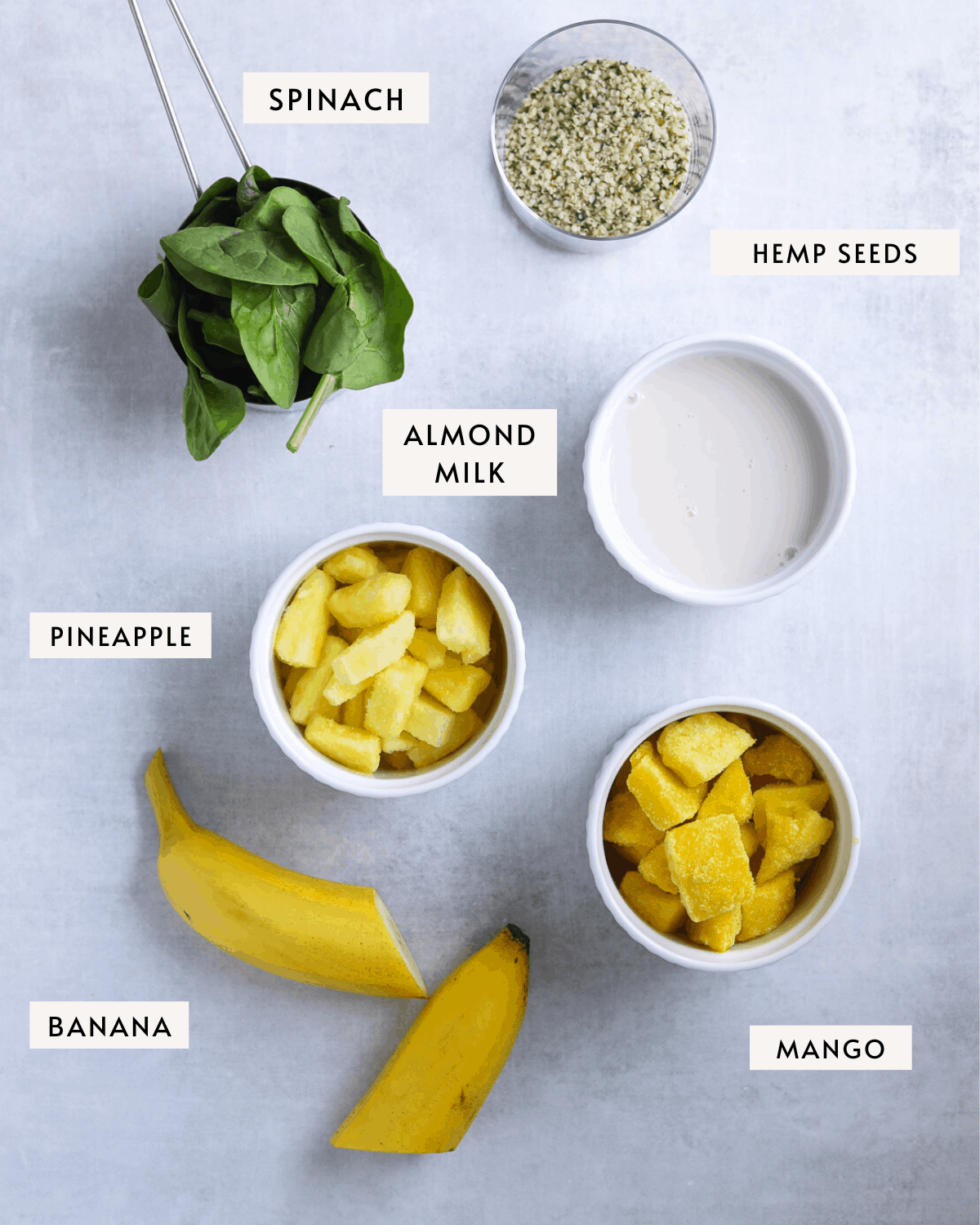 mango pineapple smoothie ingredients portioned out. mango, pineapple, banana, almond milk