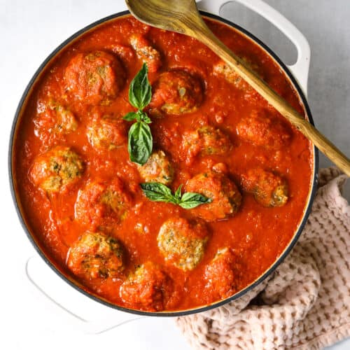 a white dutch oven skillet filled with baked meatballs, marinara sauce, fresh basil with a wooden spoon and pink towel