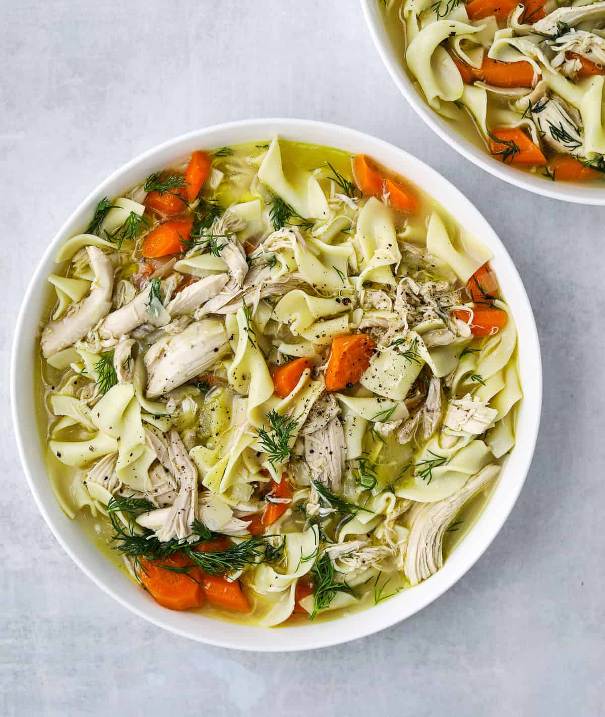 a large white bowl filled with Rotisserie Chicken Noodle Soup, fresh herb and egg noodles