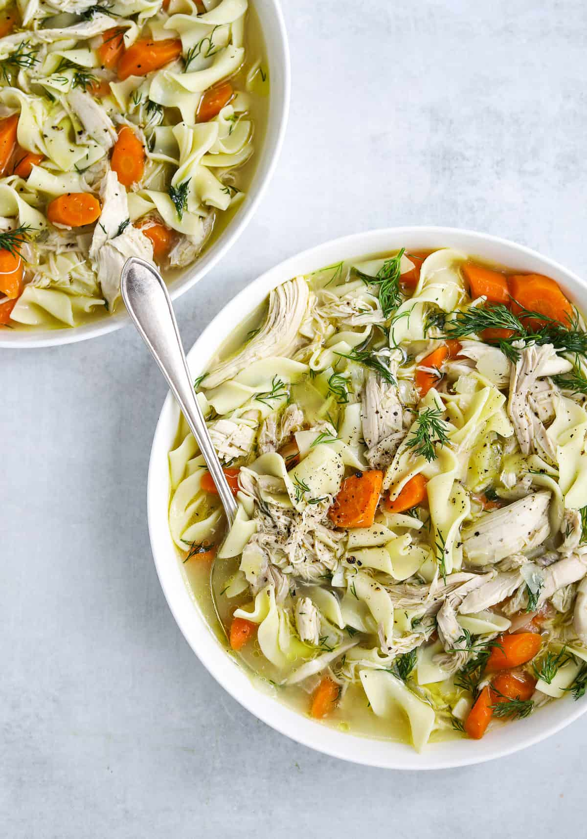 two white bowls of Rotisserie Chicken Noodle Soup one with a silver soup spoon