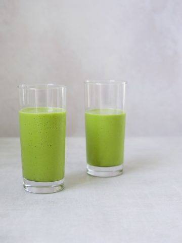 two glasses of bright green mango and pineapple smoothie on a blue background