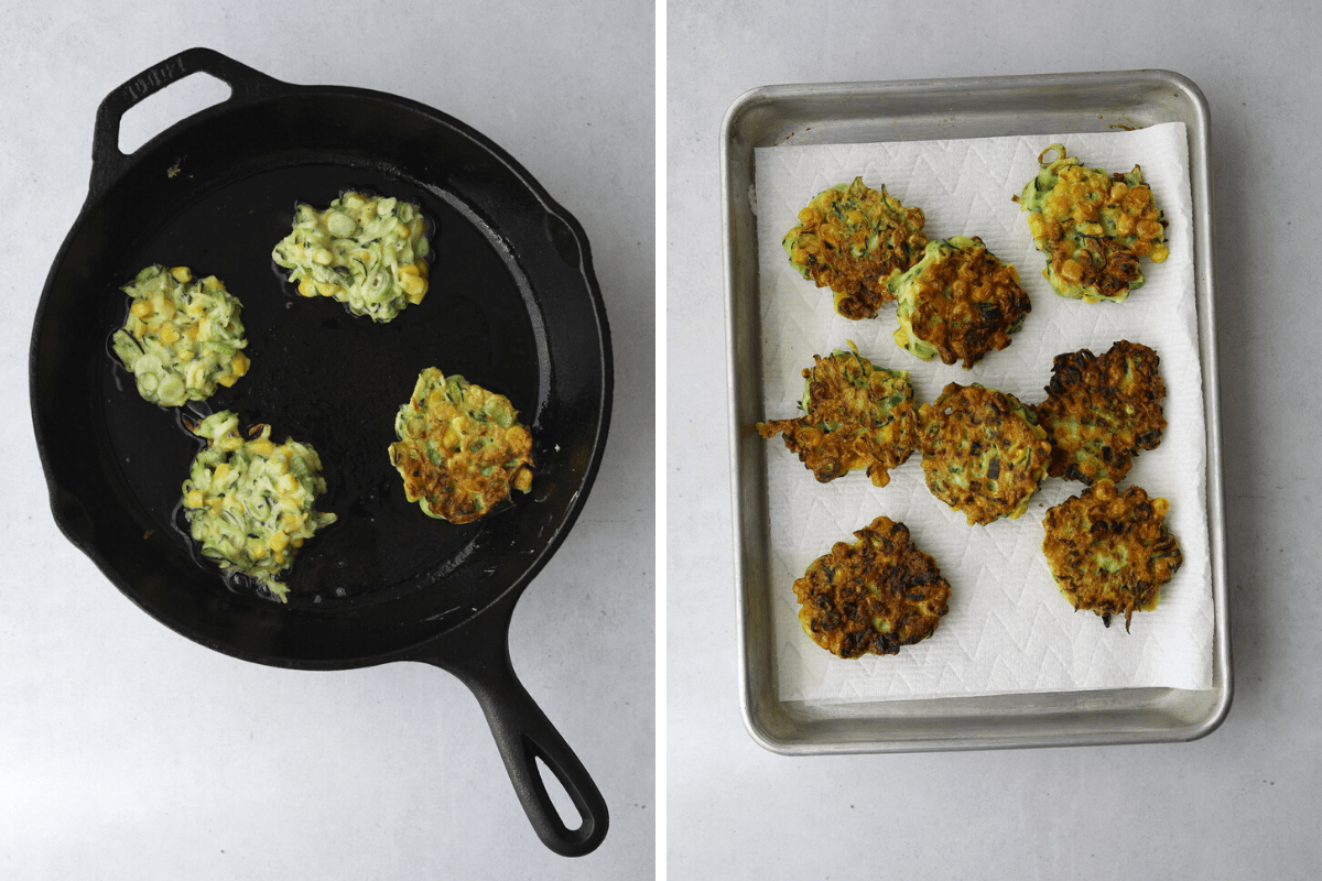 a cast iron pan frying  four corn and zucchini fritters and a baking tray lined with paper towel filled with fritters