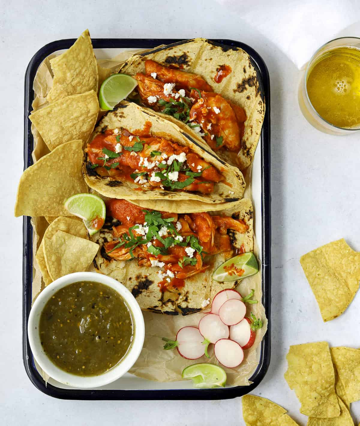a rectangle tray filled with chicken tacos, tortilla chips and a cup of salsa