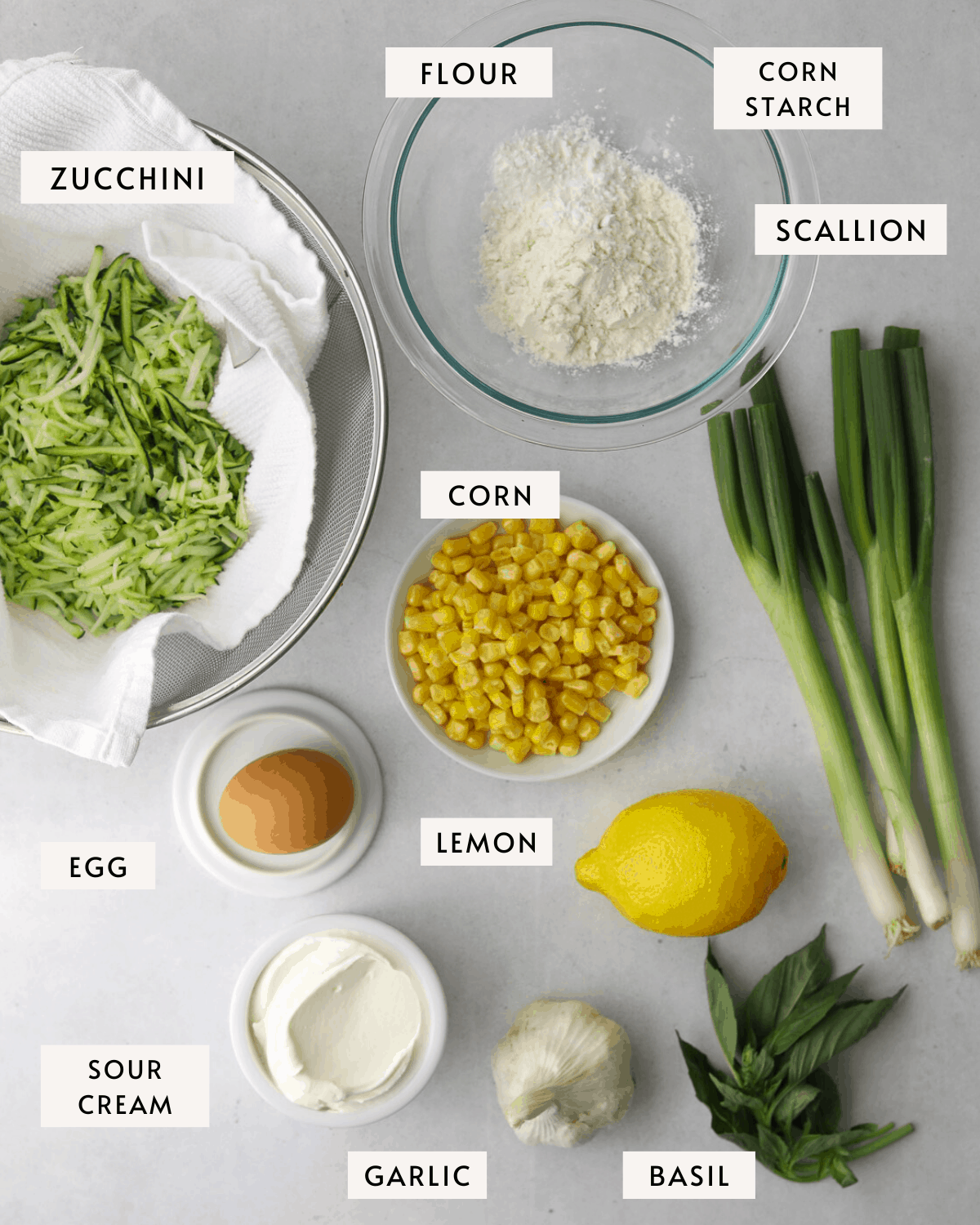 corn and zucchini fritter ingredients portioned individually; a bowl of corn, grated zucchini, flour, corn starch, egg, etc