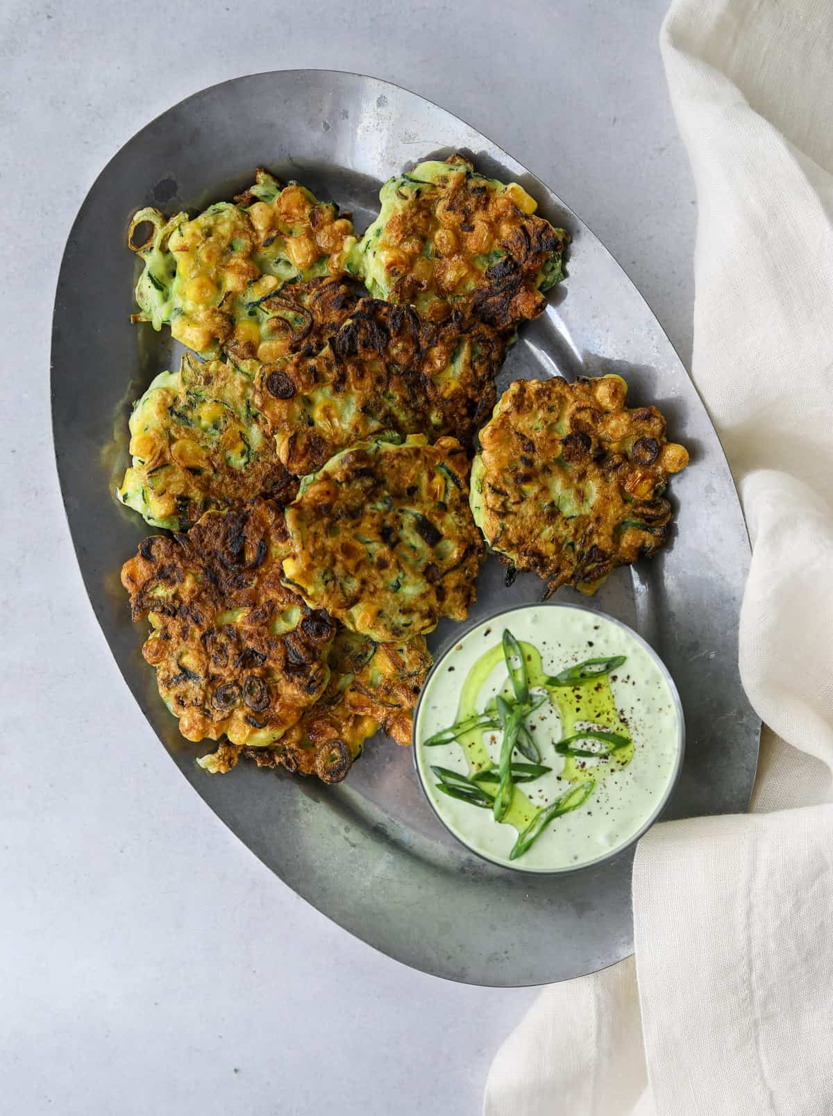an oval, silver tray filled with corn and zucchini fritters with a side of green goddess dip and a white linen napkin