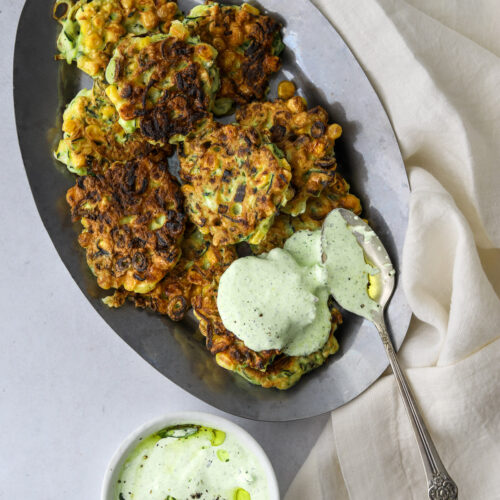 a silver platter filled with corn and zucchini fritter and green goddess dipping sauce