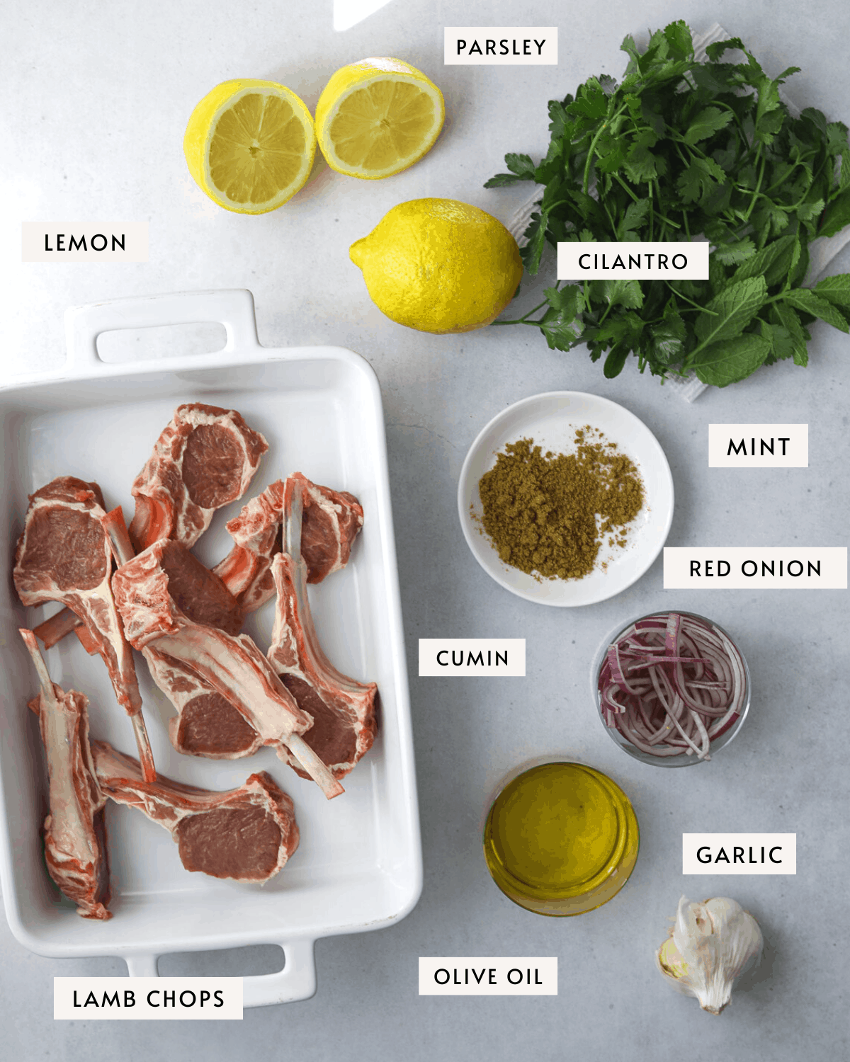 recipe ingredients, a platter of lamb chops, lemons, herbs, red onion, cumin and olive oil
