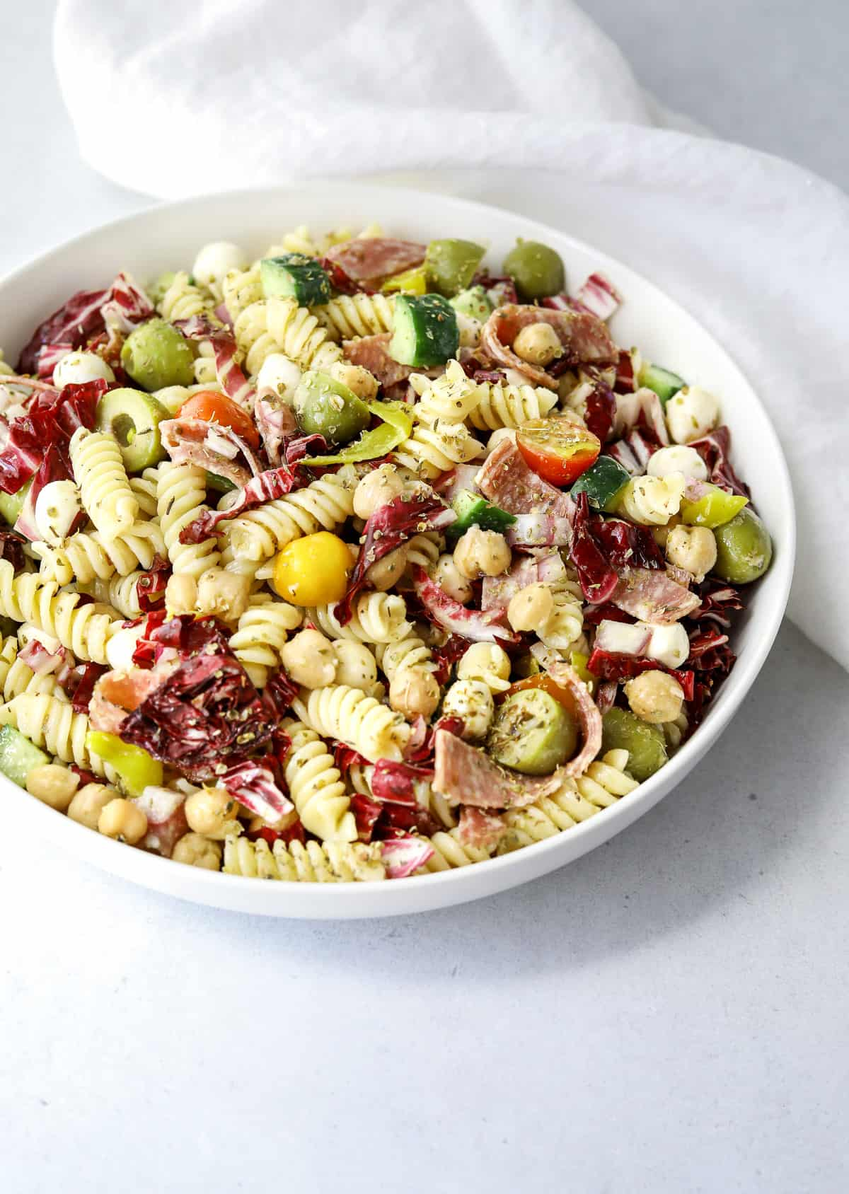 a white bowl filled with Italian Pasta Salad on a blue background