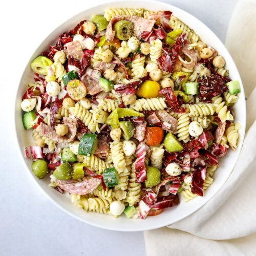 a large white bowl of Italian Pasta Salad with rotini pasta, olives, salami, mozzarella, cucumber and tomatoes