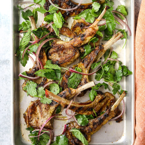 a rectangular baking tray filled with grilled lamb chops, fresh herbs and red onion