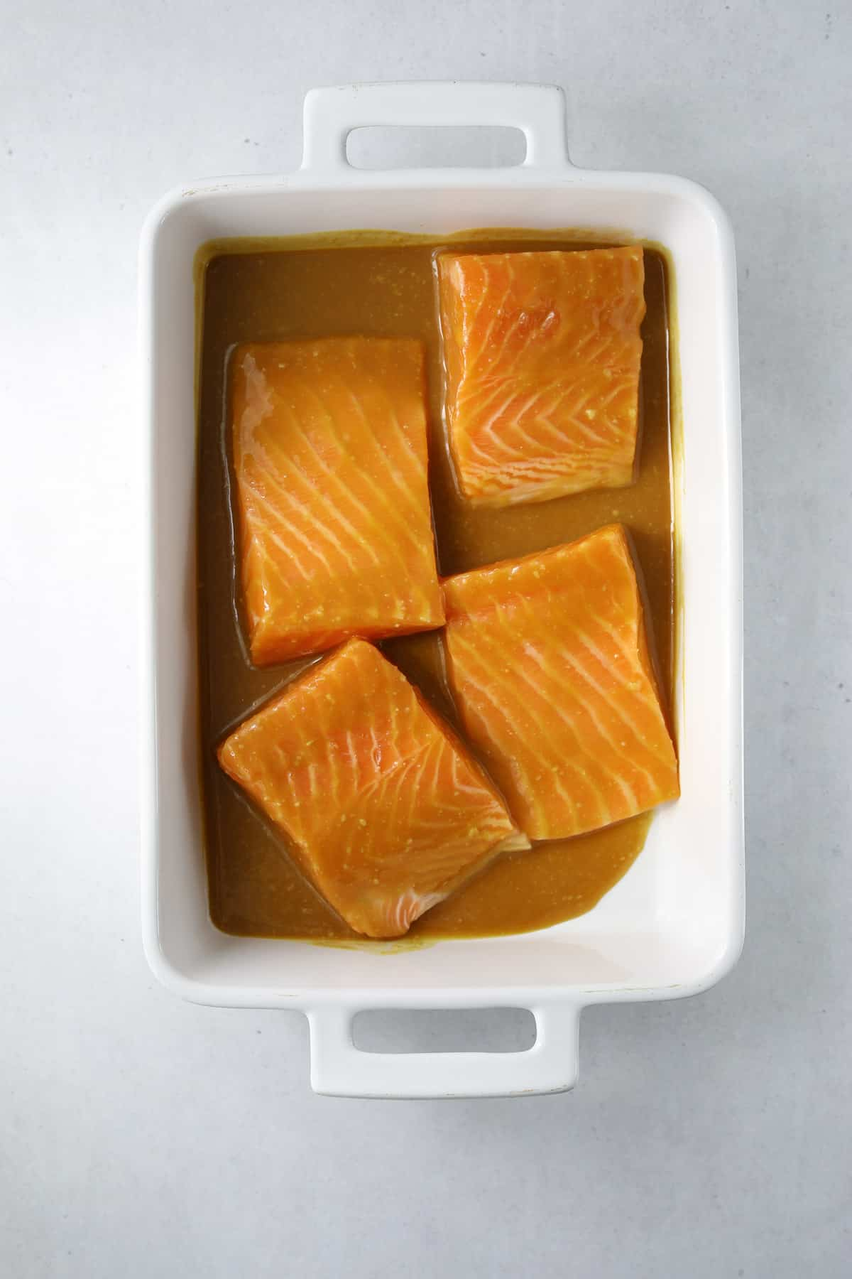 four filet of salmon marinating in a miso-honey-soy marinade in a white rectangle baking dish