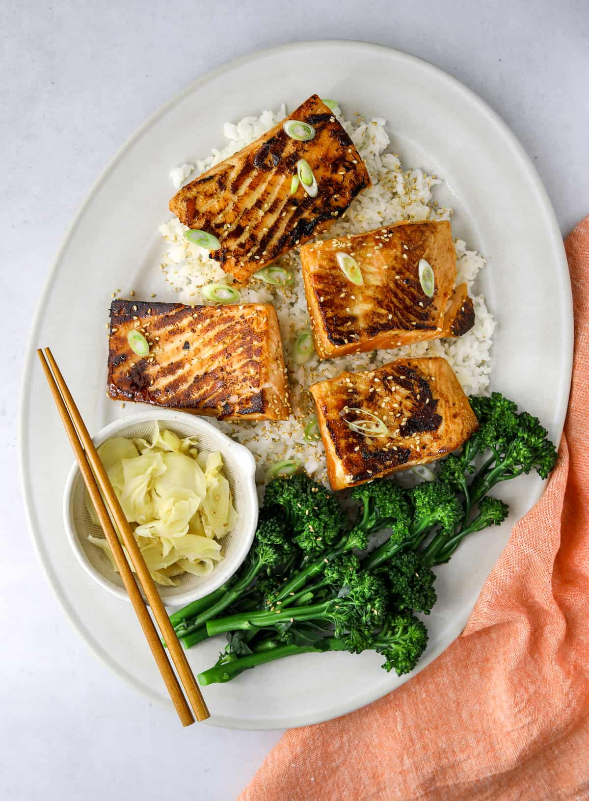 an oval platter with four pieces of miso-honey salmon, rice, broccolini and chop sticks