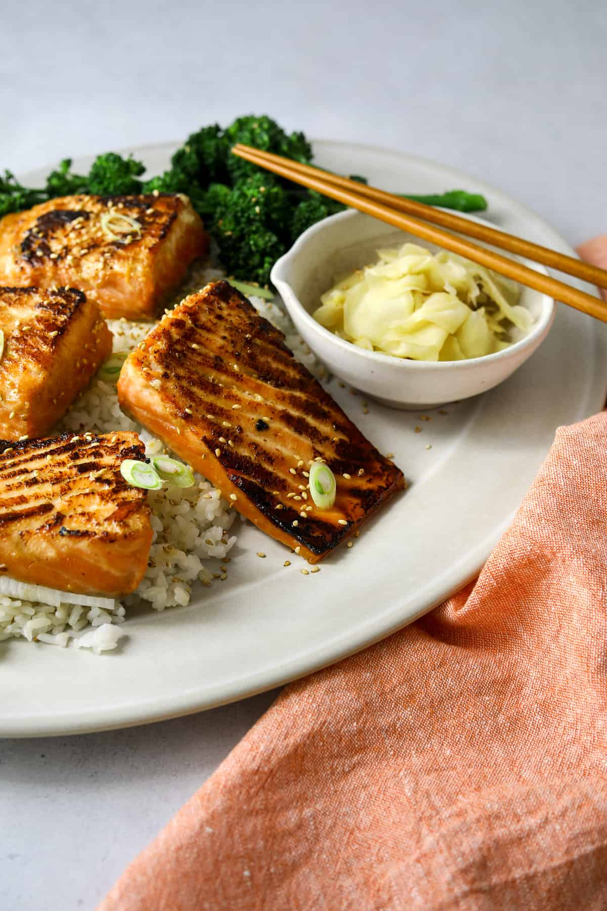 a close up view of miso honey salmon on a white platter with sushi ginger, rice and chopsticks