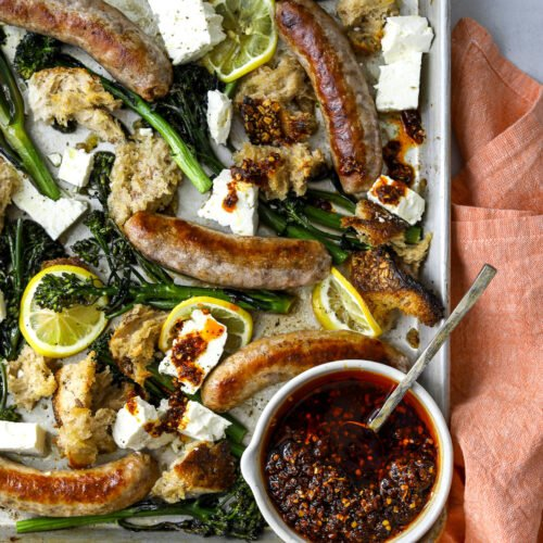 a sheet pan with roasted sausages, broccolini, lemon slices and bowl of chili oil