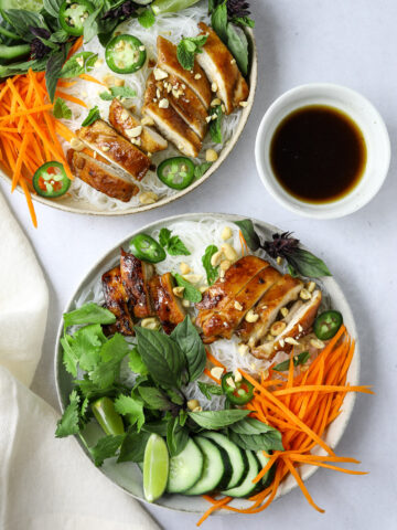 two bowls of Vietnamese rice noodle salad topped with basil, cilantro, mint and chicken