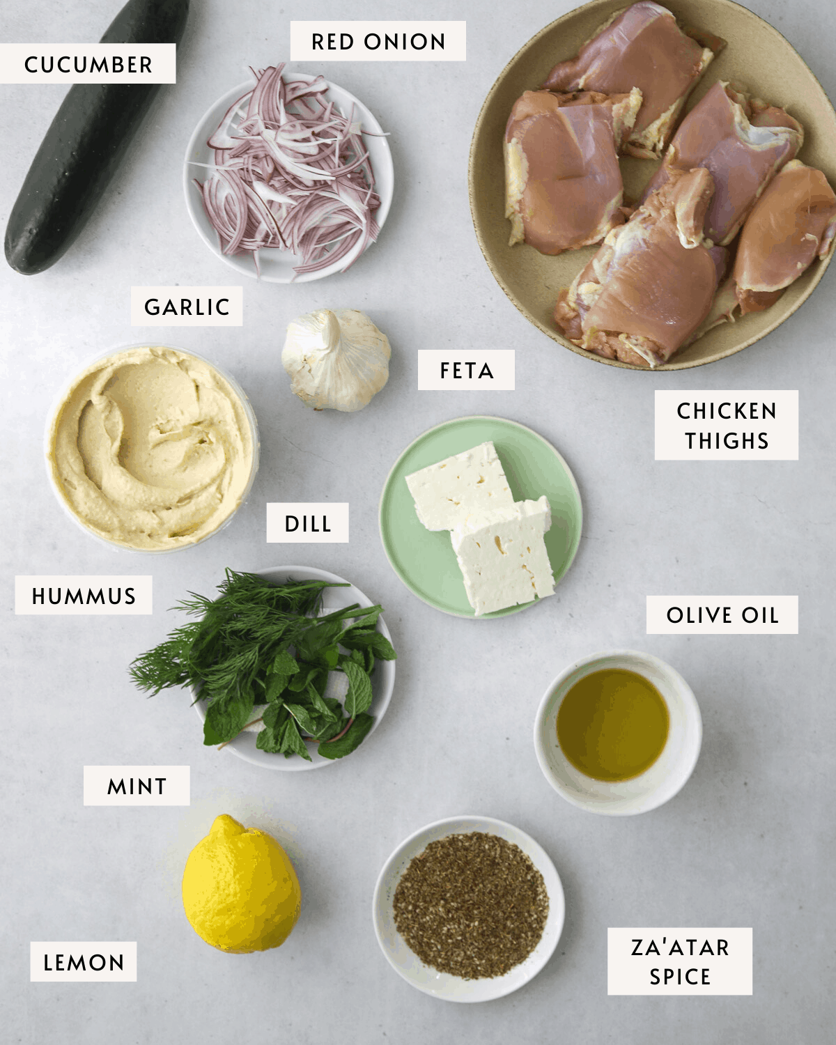 za'atar chicken bowl ingredients, a bowl of chicken thighs, store-bought hummus, feta cheese, etc