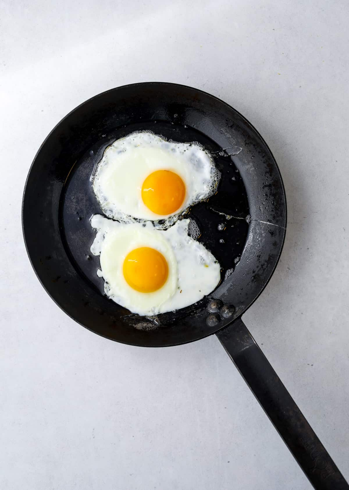 two sunny side up eggs in a cast iron pan
