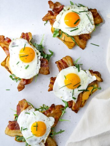 four open-faced breakfast sandwiches topped with arugula, bacon and sunny side up eggs.