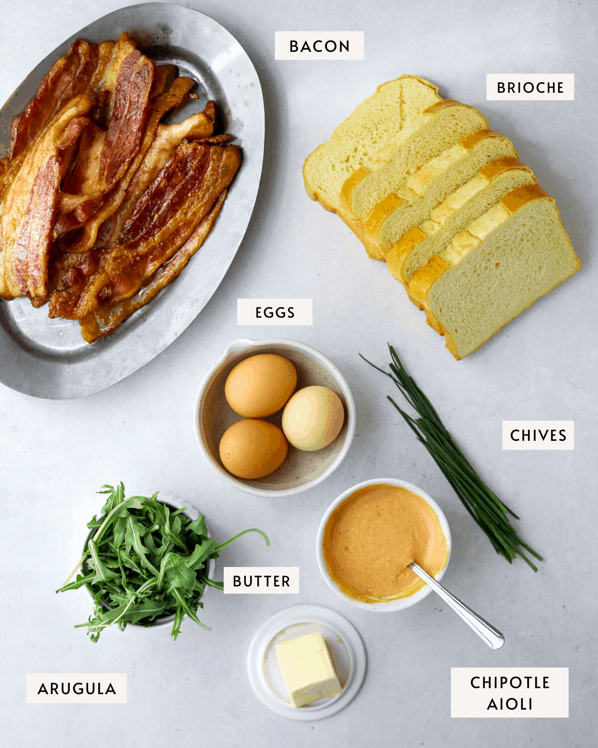 Brioche Breakfast Toast ingredients, cooked bacon, eggs, arugula, sliced brioche, aioli, chives and butter