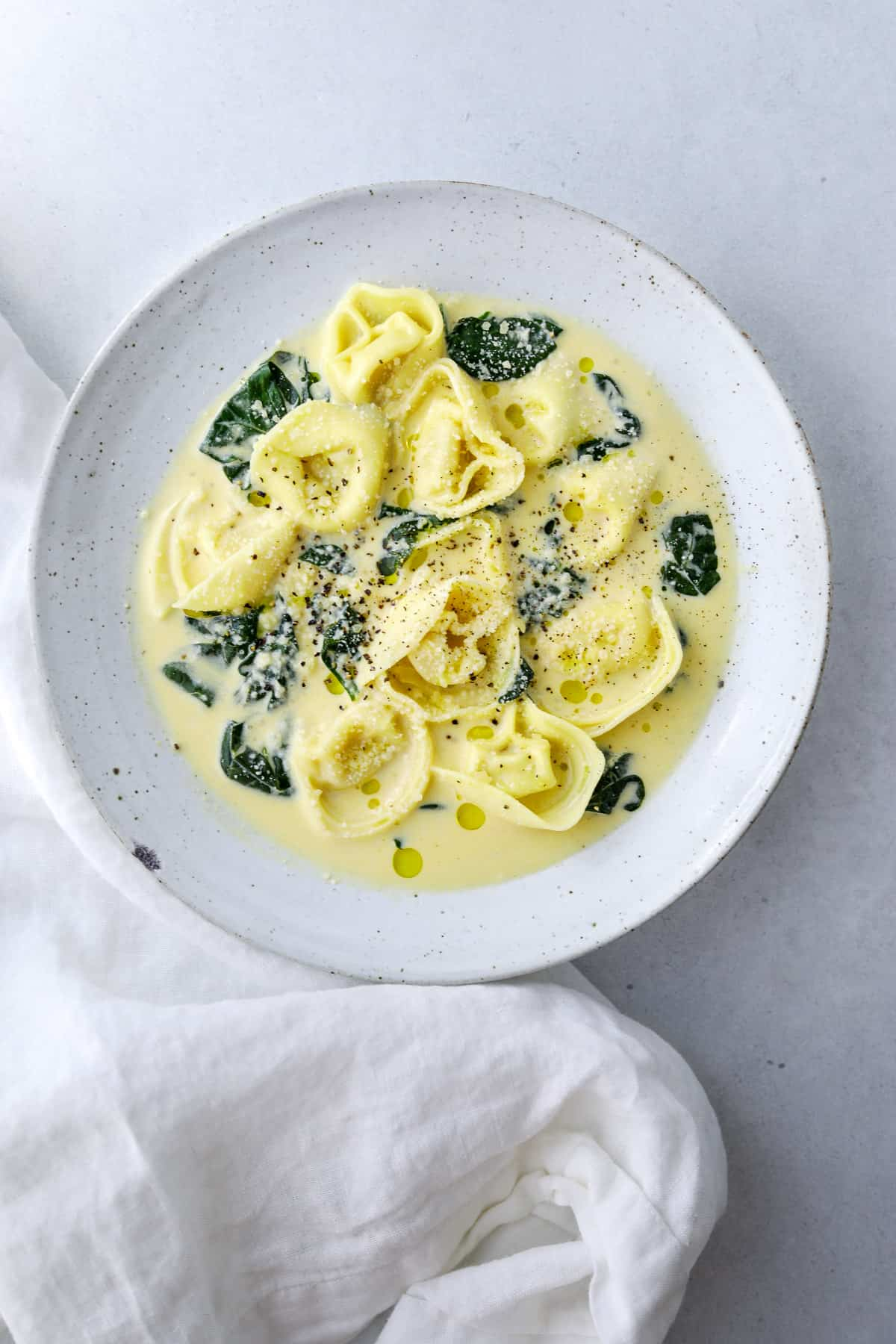 a ceramic bowl filled with a creamy soup of tortellini, spinach and topped with freshly cracked pepper and parmesan cheese