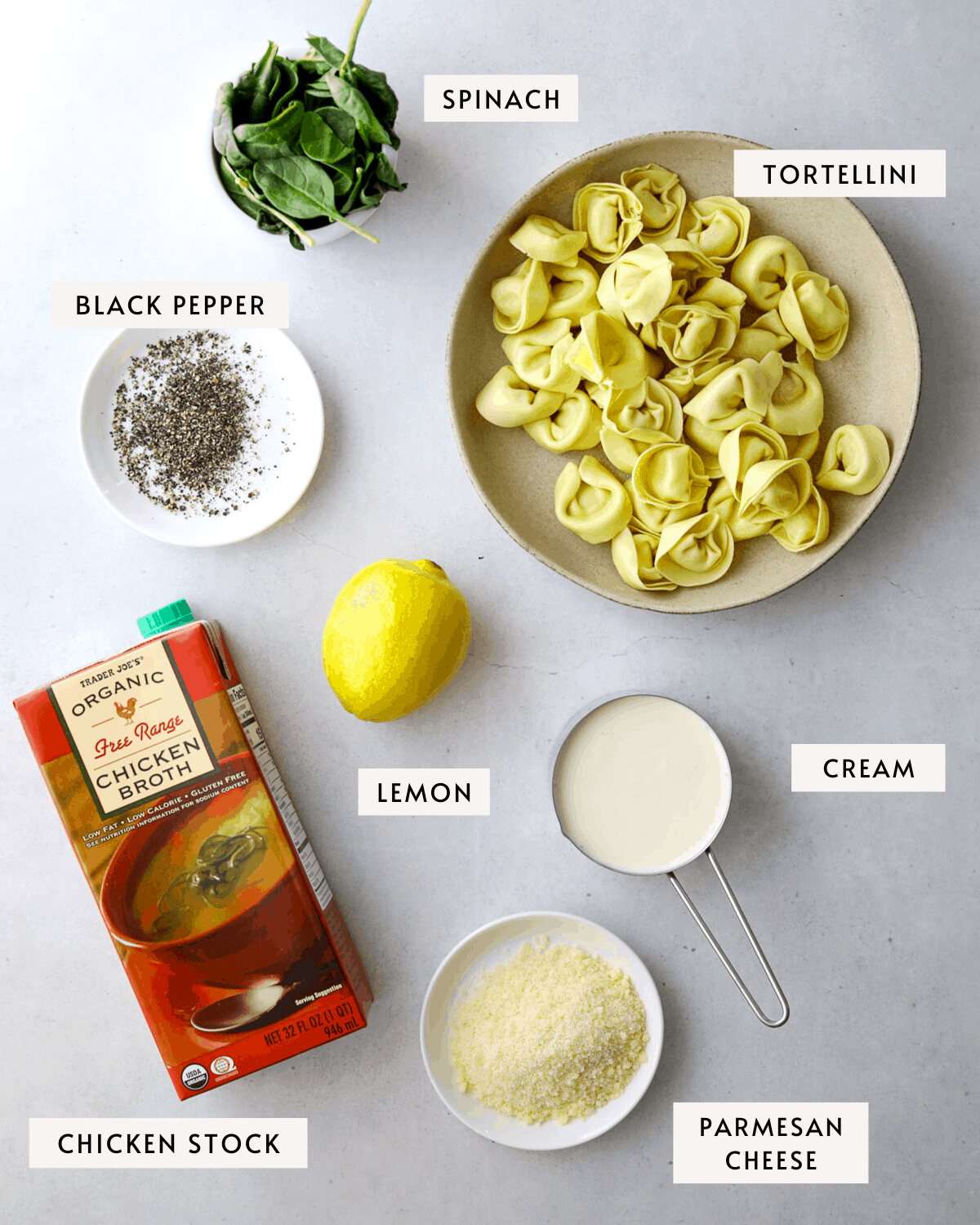 soup ingredients: a bowl of tortellini, a box of chicken broth, a white bowl with parmesan cheese, a lemon, a cup of cream, black pepper in a white bowl
