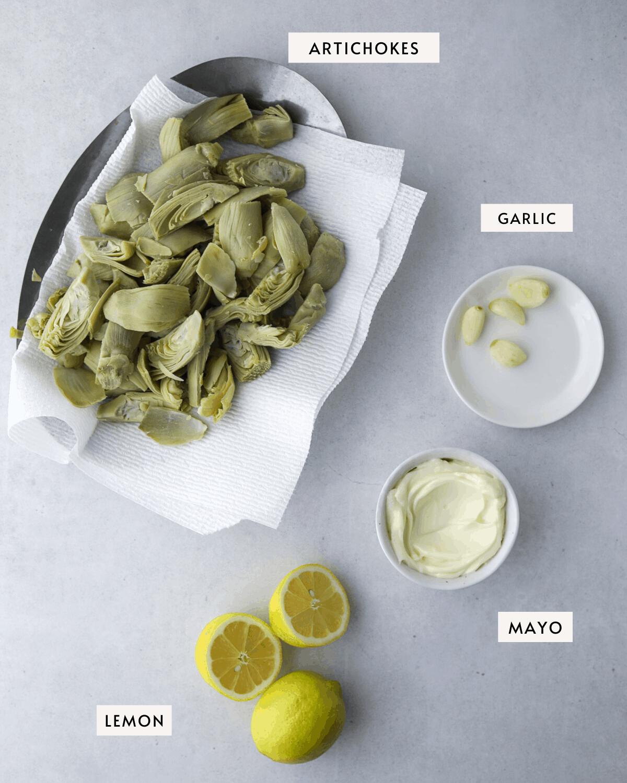 artichokes on a metal platter, a bowl of garlic cloves, a bowl of mayo, lemons