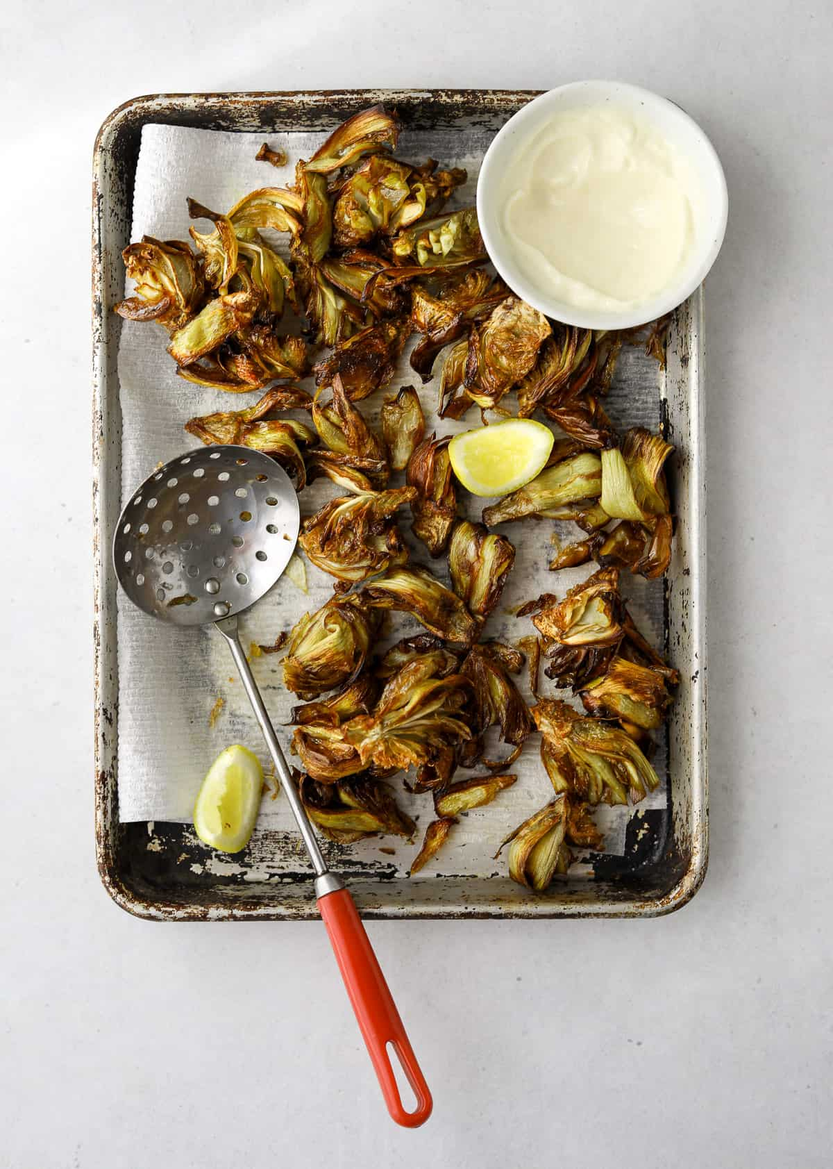 a paper towel lined baking tray with fried artichokes, lemon wedges and a bowl of lemon aioli