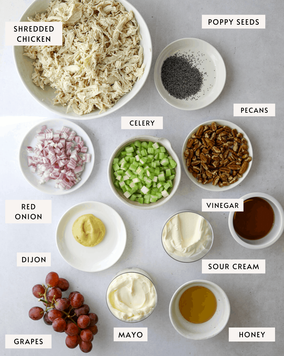 Sonoma Chicken Salad ingredients in individual bowls, shredded chicken, diced red onion, celery, grapes, toasted pecans, mayo etc