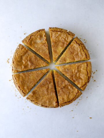 a gluten-free citrus and olive oil cake cut into six slices on a blue background