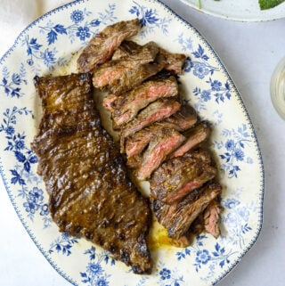 a blue and white platter filled with grilled skirt steak with a bowl of salad on the side
