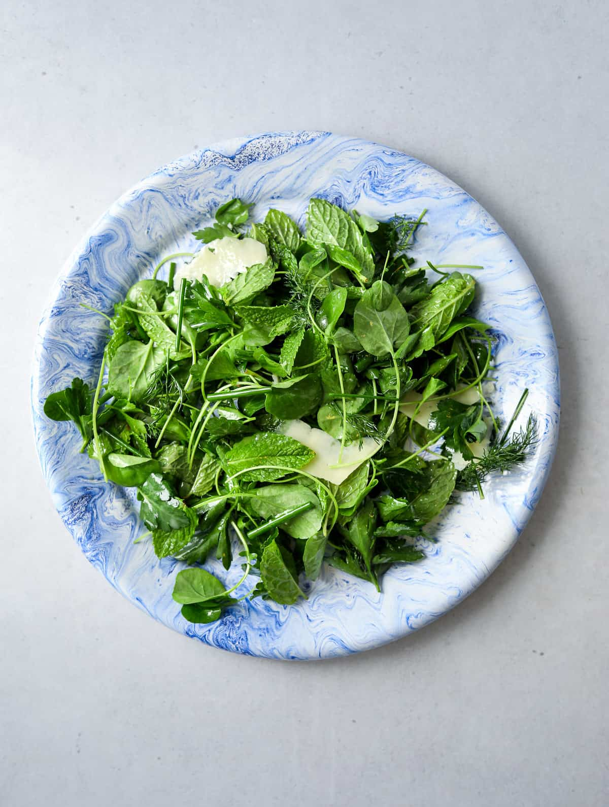 a blue plate filled with herb salad and shaved parmesan cheese