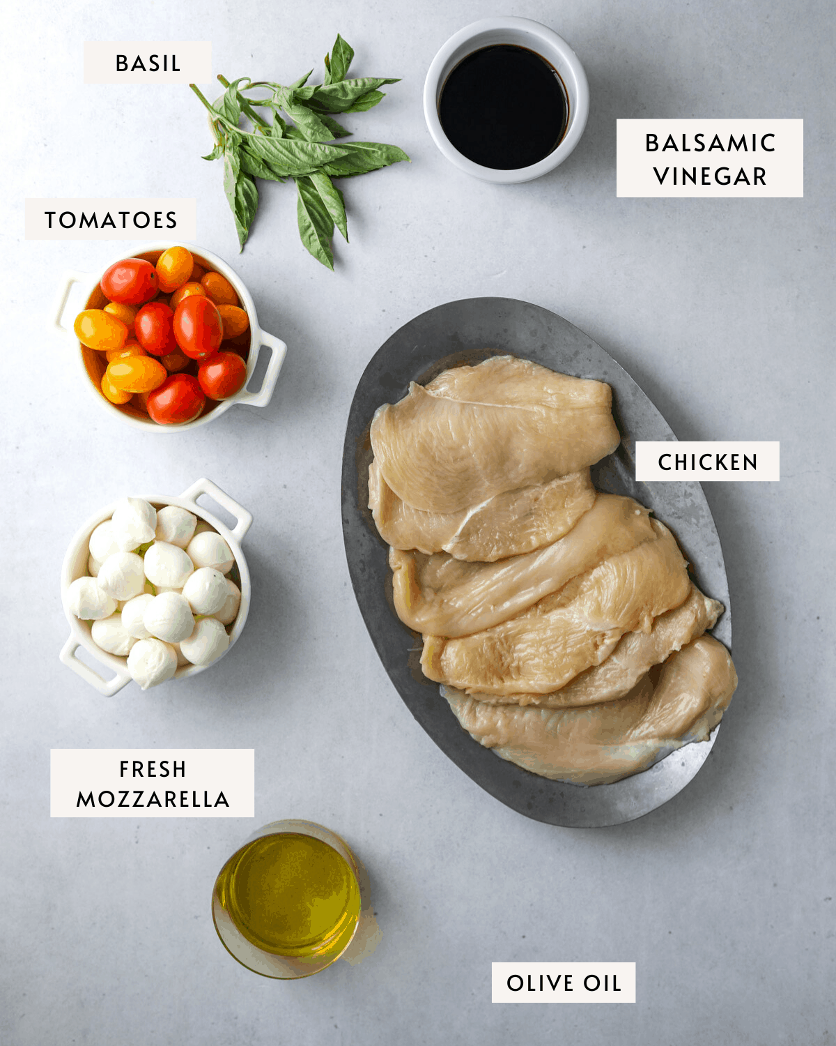 recipe ingredient mise en place: a bowl of tomatoes, a bowl of small fresh mozzarella balls, a platter of raw chicken, olive oil and balsamic vinegar