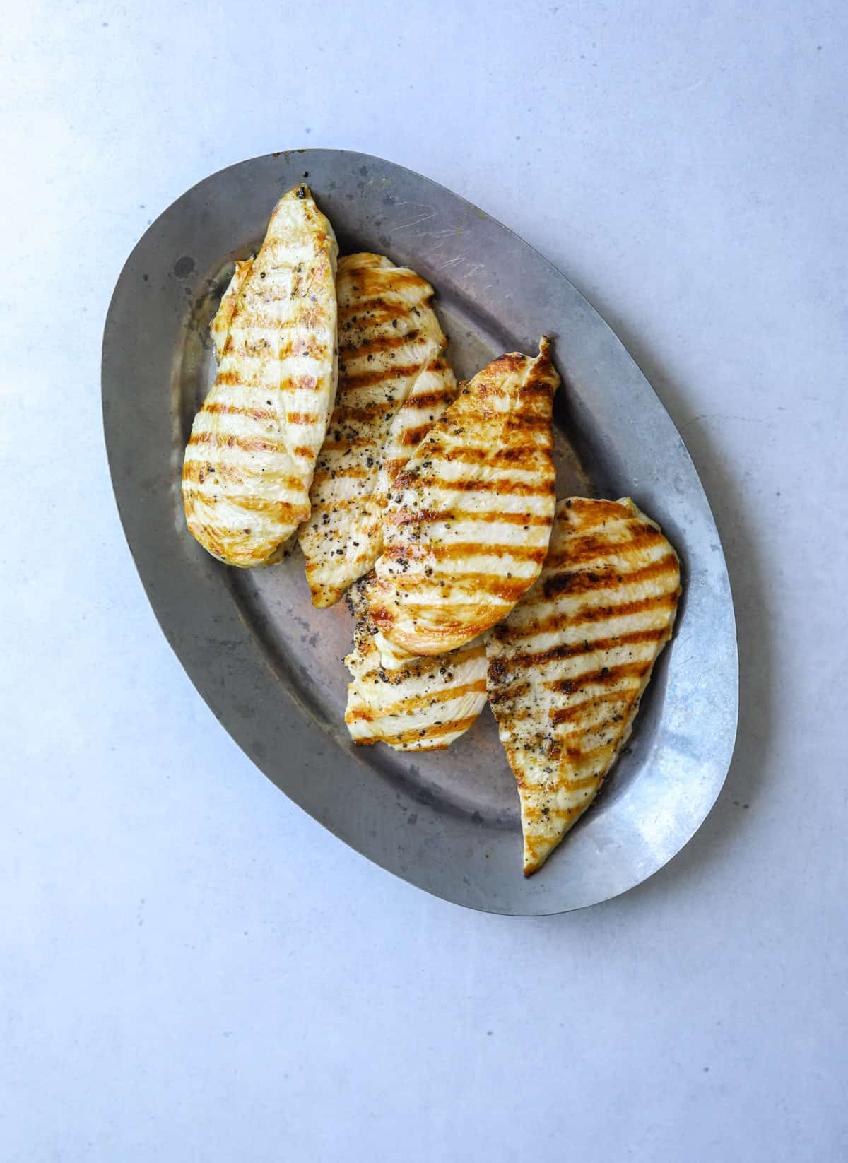 a silver platter with grilled chicken breast on a blue background