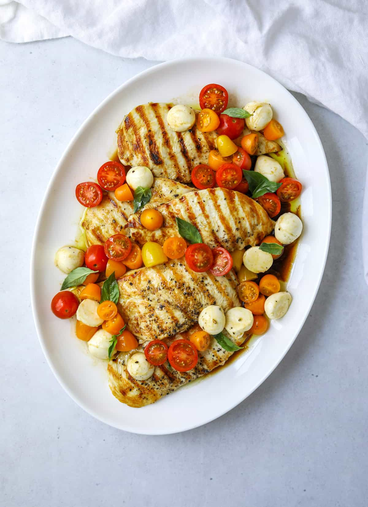 a round oval platter filled with grilled chicken breast topped with cherry tomatoes, mozzarella and fresh basil.
