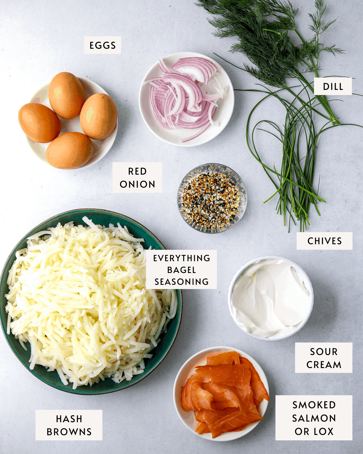 recipe ingredients individually portioned. a bowl of hasbrowns, a cup of sour cream, a plate of smoked salmon, 4 eggs, herbs and onion.