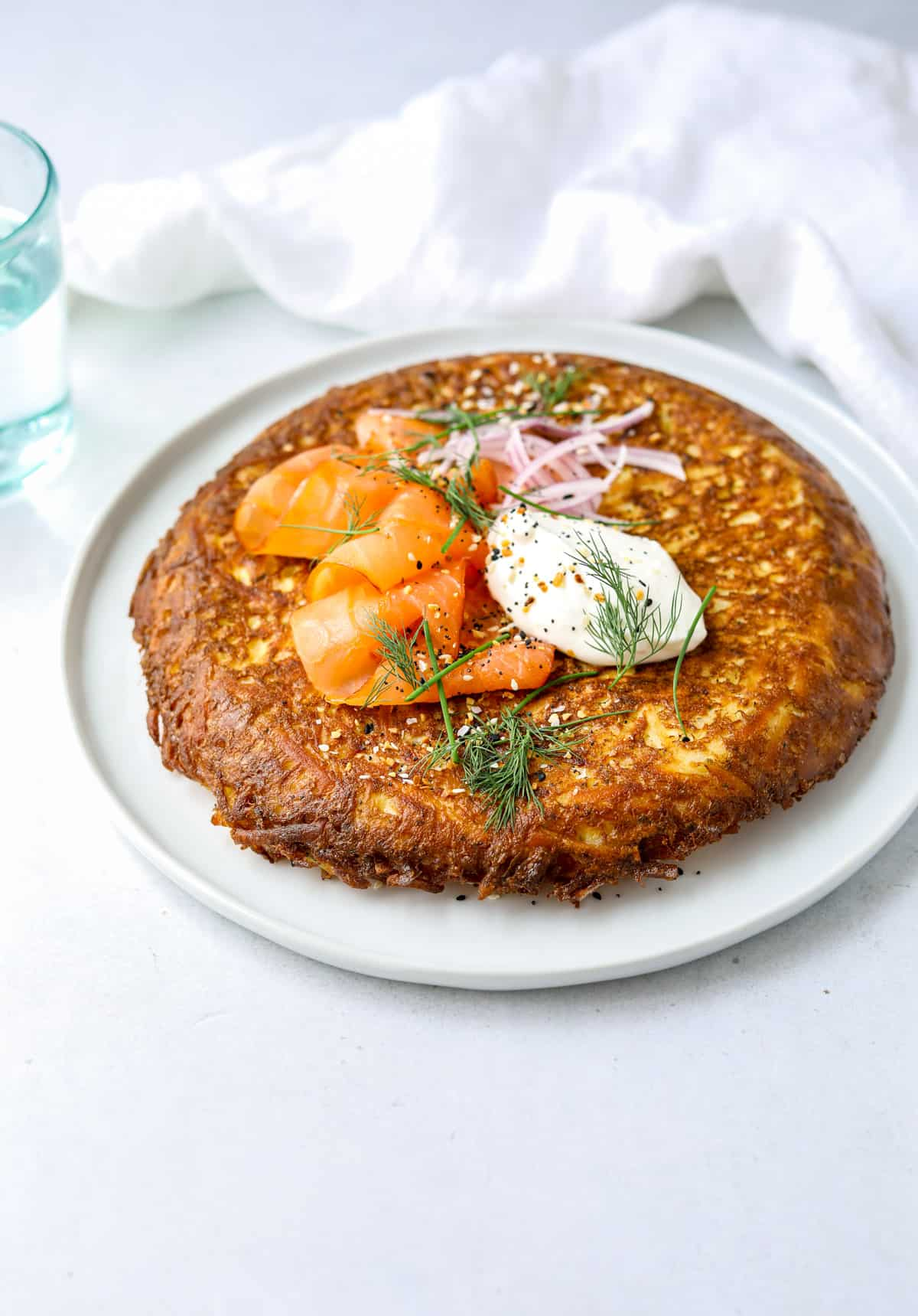 a hash brown frittata on a white plate topped with sour cream, smoked salmon and fresh herbs with a blue glass pitcher in the background and a white cloth napkin
