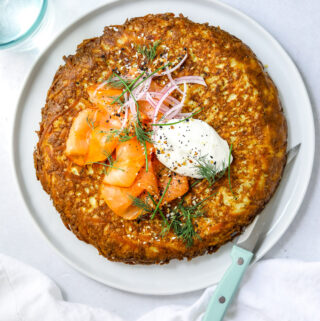 a white plate filled with a crispy, golden brown hash brown frittata topped with smoked salmon, a dollop of sour cream and fresh herbs. blue knife on the side, white background.
