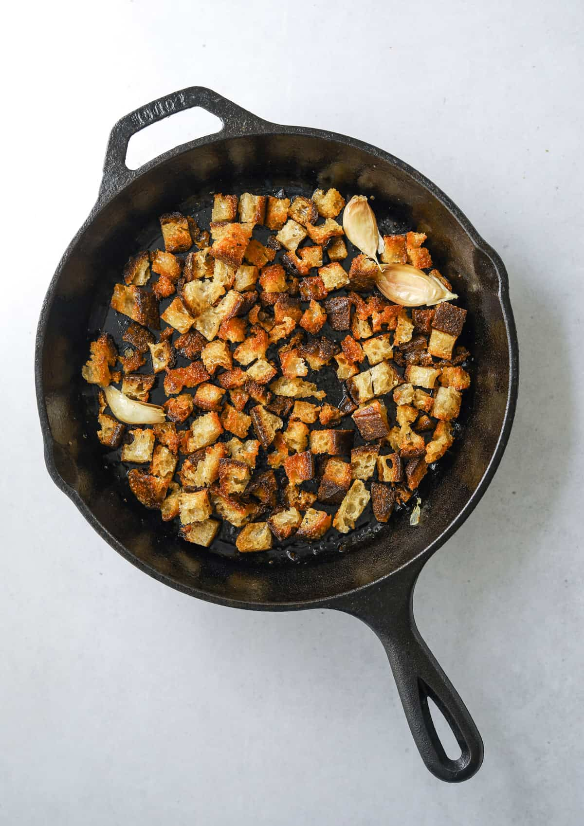 cubed crouton and whole garlic cloves cooking in a cast iron pan.