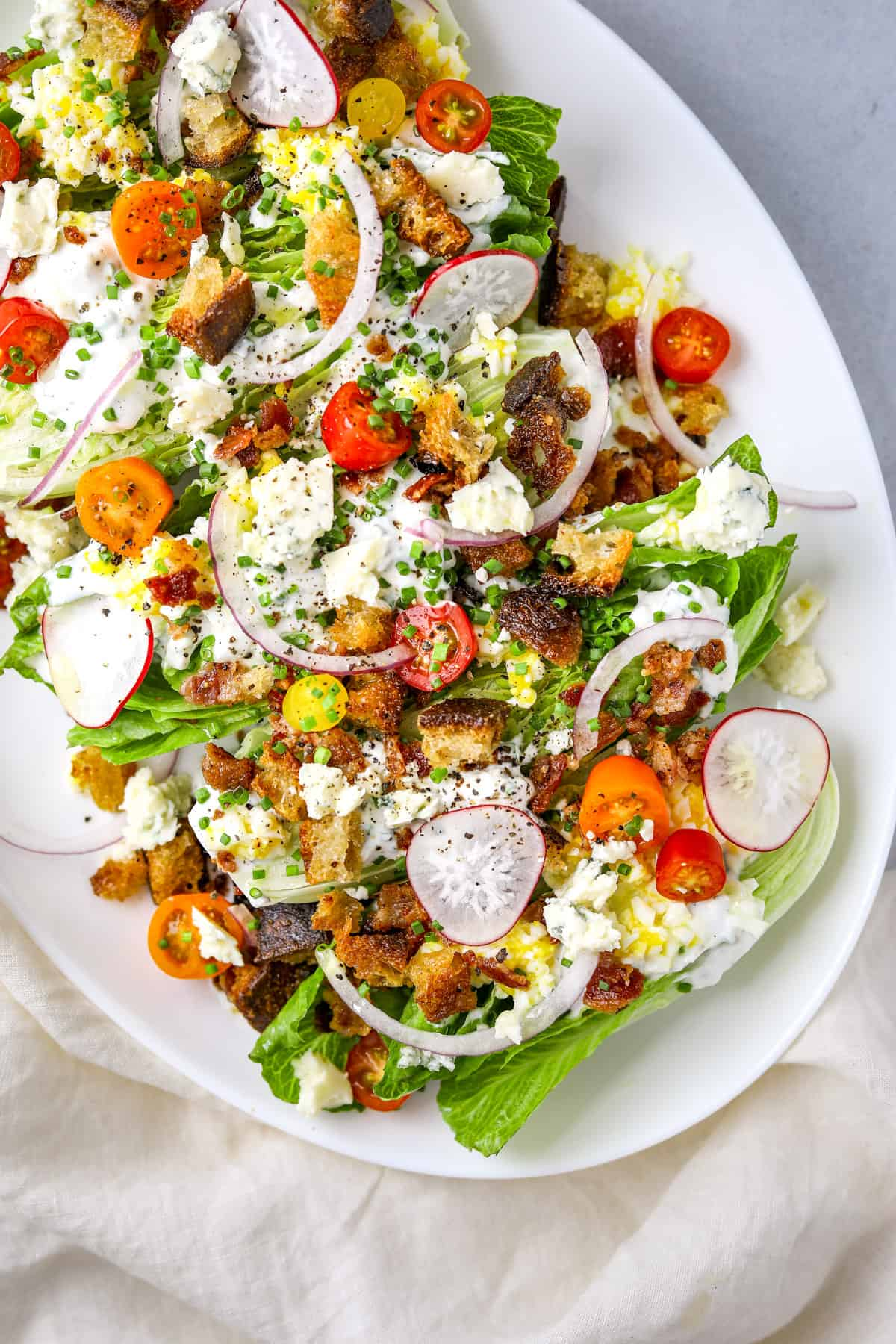 a bright and colorful little gem salad topped with cherry tomatoes, blue cheese dressing, croutons and radish on a white platter oval
