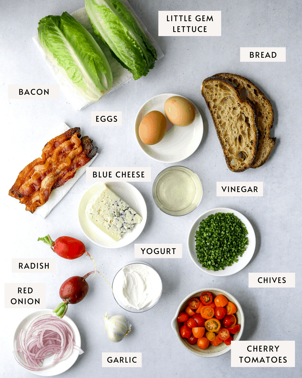 recipe ingredients on a blue background, bread, lettuce, hard boiled eggs, yogurt, bacon, cherry tomatoes, and chives.