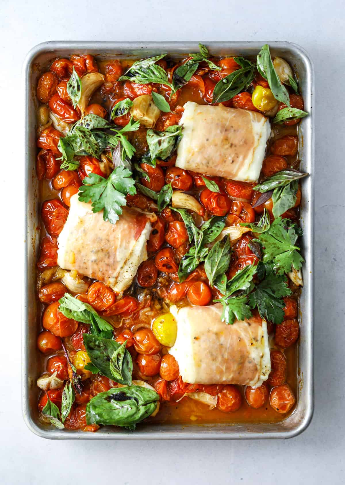a sheet tray with Prosciutto Wrapped Halibut with Slow-Roasted Tomatoes