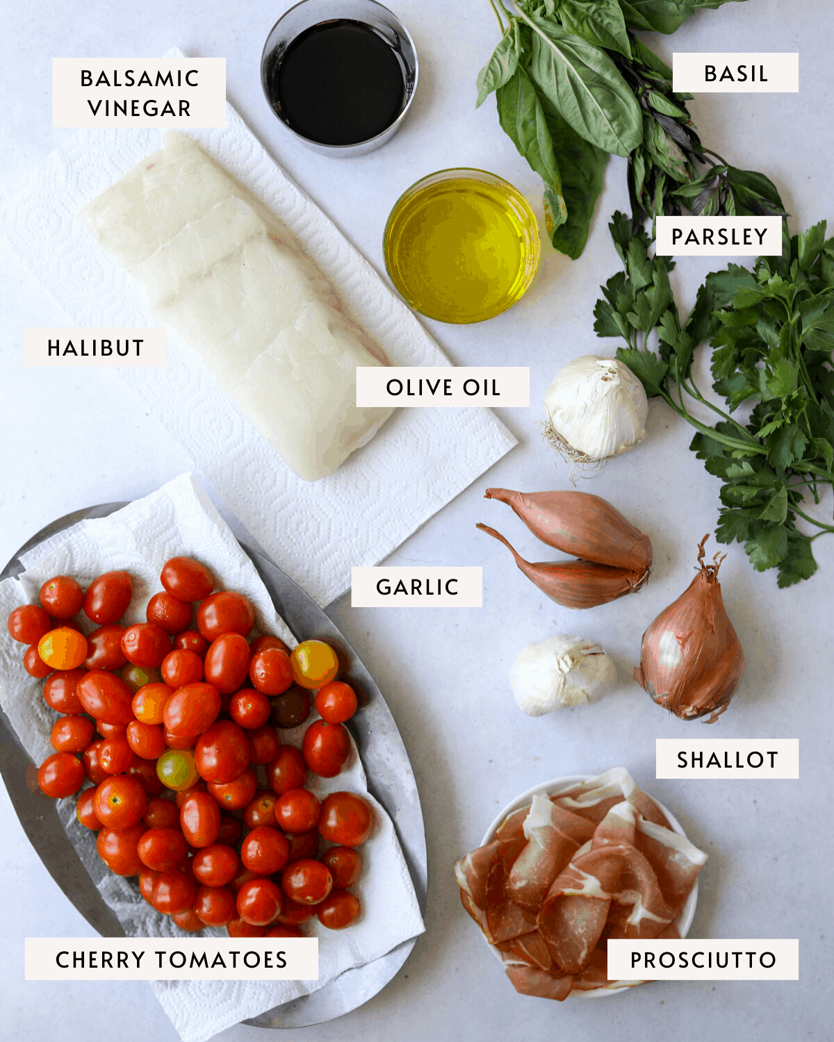 recipe ingredients individually portioned, cherry tomatoes on a platter, halibut, shallots, prosciutto, fresh basil and parsley.