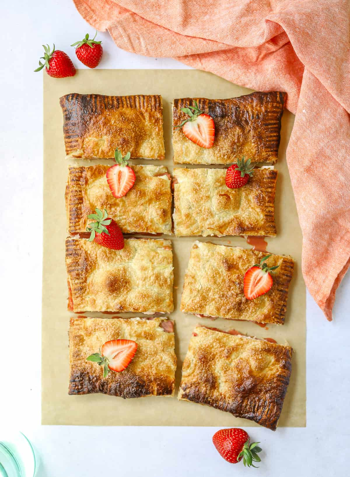 a strawberry rhubarb puff pastry tart cut into 8 rectangles on a blue background with fresh strawberries on top and a pink cloth napkin
