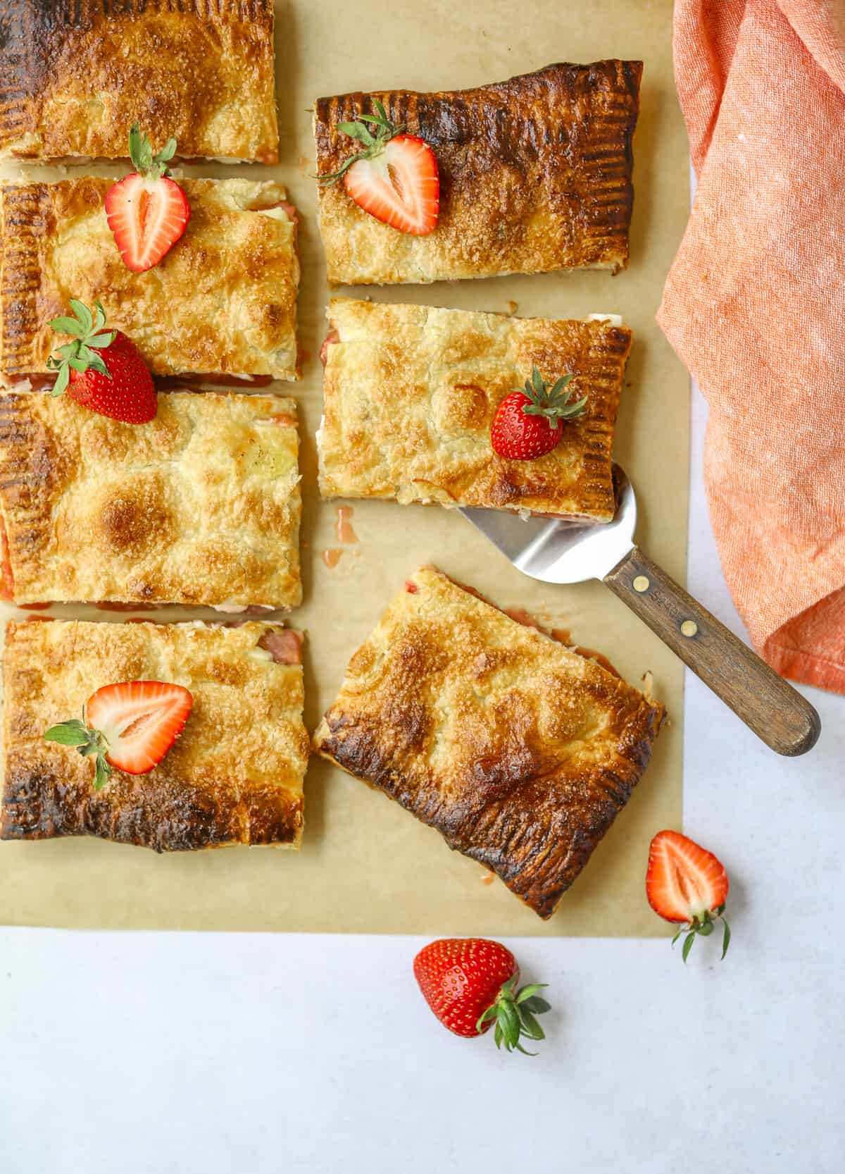 a Strawberry Rhubarb Puff Pastry Tart cut into slices with fresh strawberries on top on a blue background with a pink cloth napkin on the side